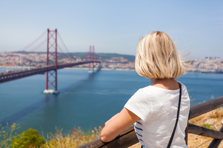 Female traveler enjoys panoramic views of Lisbon and the bridge of April 25 Stock Photo