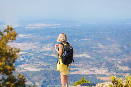 Female traveler with a backpack on her back enjoying the views from the mountains of Montserrat in Spain