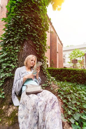 Beautiful young woman sitting leaning on a tree in the middle of ivy