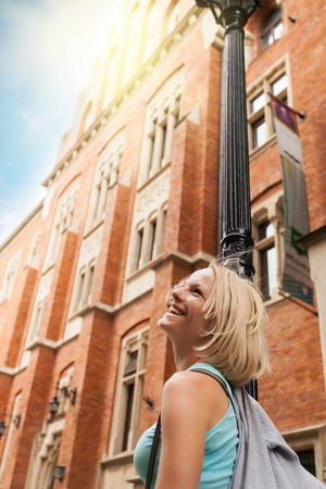 collegium: Young beautiful woman walking down the street along an old brick building against the background of sunlight Stock Photo