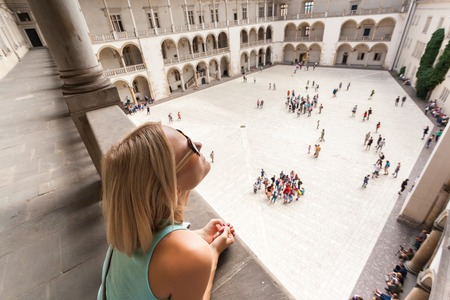 Female traveler on the background of Arcades in Wawel Castle in Cracow.