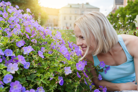 Female traveler sitting and sniffing flowers on the background of Wawel Castle