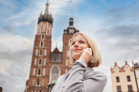 Young beautiful woman on the background of the St. Marys Church in Krakow