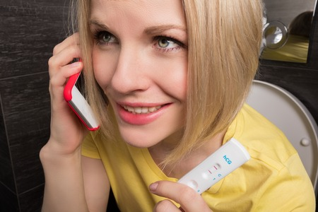Woman is sitting on the toilet and holding a positive pregnancy test and mobile phone