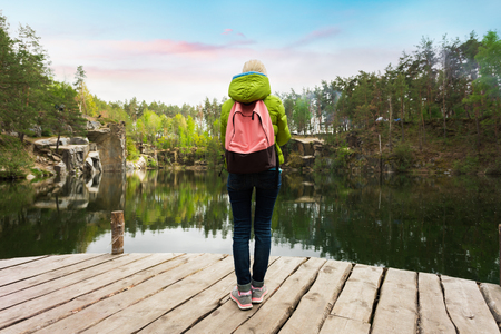 A female traveler is standing on a wooden pier near a beautiful lake in a pine forest.