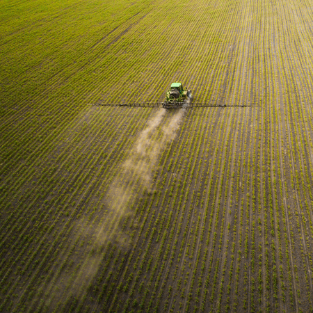 The tractor spraying the field with chemicals in the spring Stok Fotoğraf