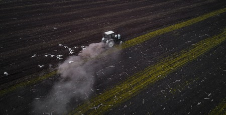 Tractor cultivating field at spring, aerial view Stock Photo