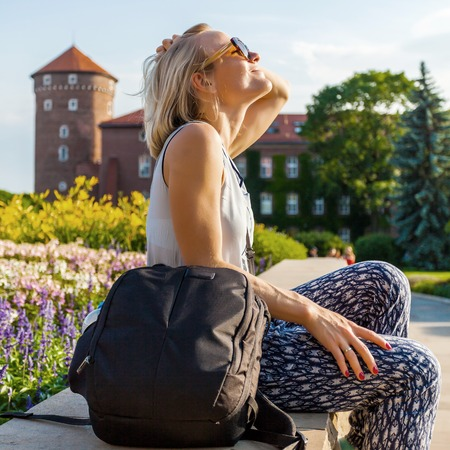 Female traveler sitting and enjoys the view of Wawel Castle.