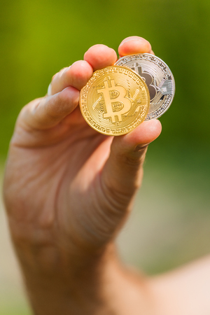 A mans hand holds a gold and silver coin bitcoin Stock Photo