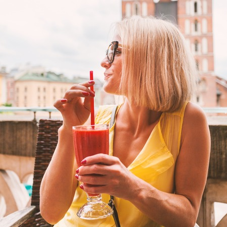 Woman drinking cocktail in front of St Marys church in Krakow. Poland.