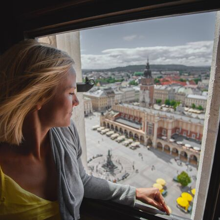 Woman looking through the window at the Market Square in Krakow