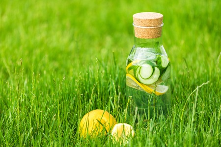 Detox drink from lemon and mint with cucumber on a background of green grass Standard-Bild