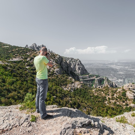 Male traveler enjoying the views from the mountains of Montserrat in Spain and makes a photo