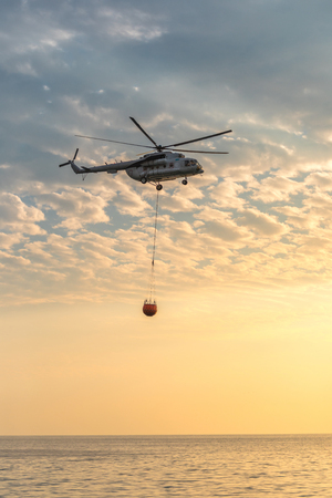A fire helicopter collects water into the sea Stock Photo