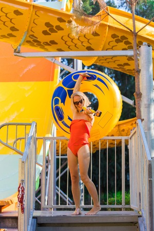 A young woman came down from the water slide with a rubber circle and a camera in her hand. 스톡 콘텐츠
