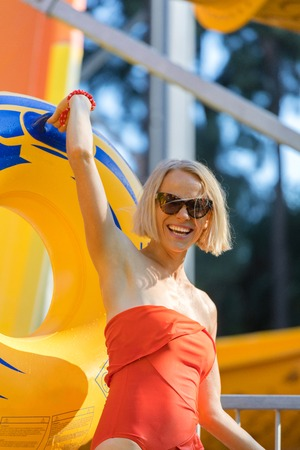 A young woman came down from the water slide with a rubber circle and a camera in her hand. Stock Photo