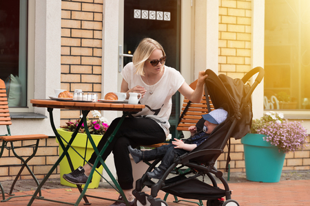 Young mother with her one-year-old child in a street cafe