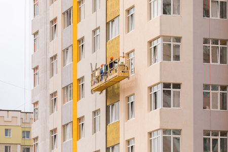 Builders paint the facade of a high-rise residential building