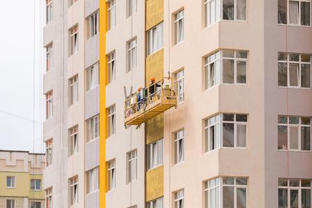 Les constructeurs peignent la façade d'un immeuble résidentiel de grande hauteur