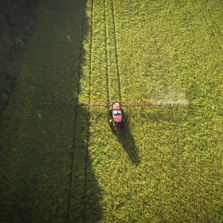 Agricultural machinery in the field. Tractor with a sprayer. Aerial view Stock Photo