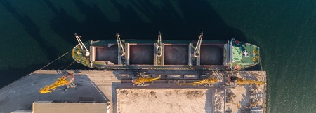 Top view of the port harbor with cargo ship on the pier and loading and unloading area, storage area