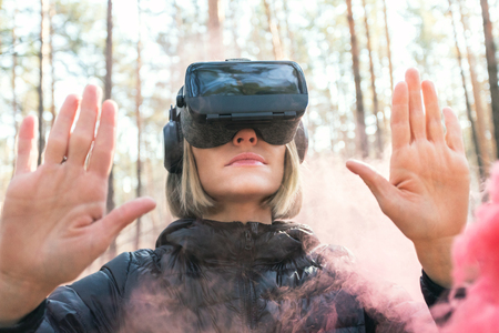 A woman wearing virtual reality goggles in the forest sees smoke bombs. VR glasses.