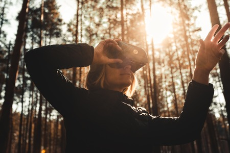 Woman in forest with virtual reality headset looking straight and trying to touch something with her hand