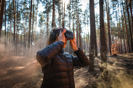 Woman in forest with virtual reality headset looking straight with orange smoke from smoke bombs