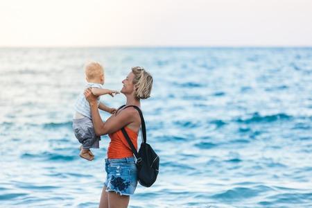 Madre e hijo caminando por la playa al atardecer