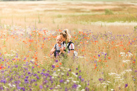 Mother and child playing in the field with flowers. Stockfoto