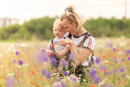 Matka i dziecko bawiące się w polu z kwiatami.