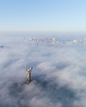 Aerial view of the Monument Motherland, shrouded in thick fog. Historical sights of Ukraine. Imagens