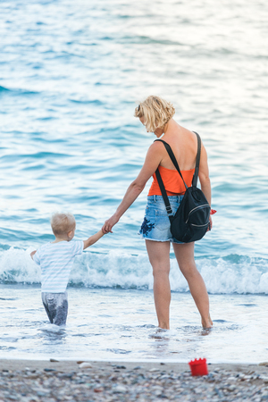 A young and beautiful mother walks in the fresh air on the beach with her young child. The boy squatted down to get a pebble he liked at sunset time. The concept of a happy family, lifestyle, vacation at sea, walking in the fresh air with children