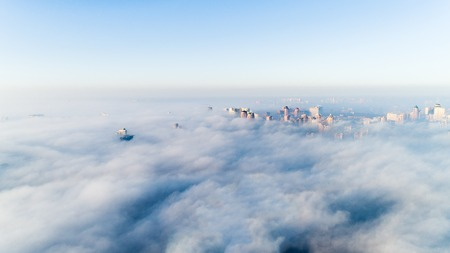 The city is covered with thick fog and protruding from it where neither where high-rise buildings