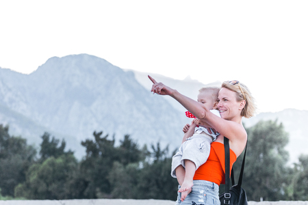 Young mother holding her little son in her arms and shows him something with her hand in the distance against the backdrop of a mountain landscape