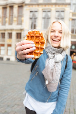 Young beautiful woman holding a traditional Belgian waffle on the background of the Great Market Square in Brussels, Belgium Archivio Fotografico