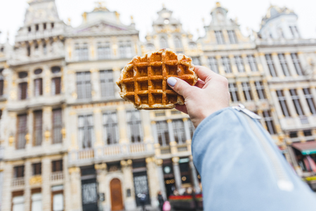 Traditional Belgian waffle on the background of the Grand-Place, Belgium