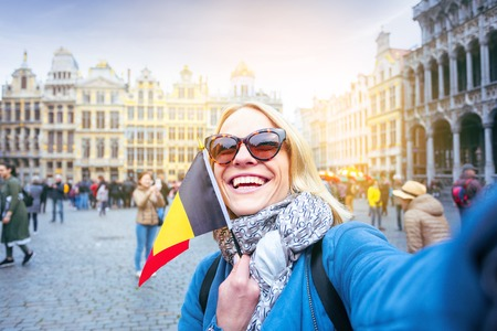 Woman tourist stands with the flag of Belgium on the background of the Grand-Place or the Grand Market Square in Brussels