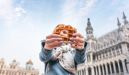 Young beautiful woman holding a traditional Belgian waffle on the background of the Great Market Square in Brussels, Belgium 写真素材
