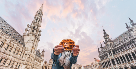 Young beautiful woman holding a traditional Belgian waffle on the background of the Great Market Square in Brussels, Belgium Zdjęcie Seryjne