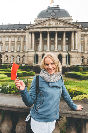 A female tourist stands with the flag of Belgium against the backdrop of the Royal Palace in Brussels. Imagens