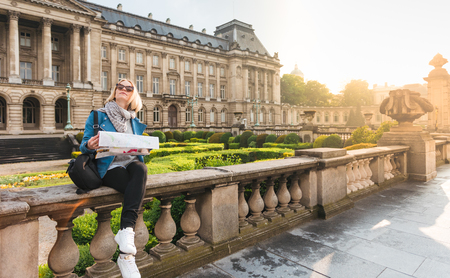 Girl sitting with a map on the background of the Royal Palace in Brussels, Belgium