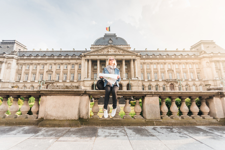 Female traveler sits on the parapet on the background of the Royal Palace in Brussels and looks into the map, Belgium Imagens