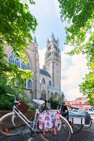 Beautiful view of the Cathedral of St. Salvator in Bruges with bright green tree crowns and sun rays and a cute bicycle parked in front of the cathedral, Belgium. Travel to Belgium
