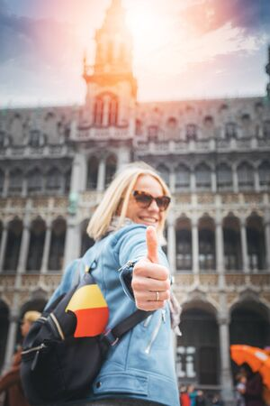 A female traveler stands on Grand Place Square in Brussels and shows her thumbs up, Belgium.