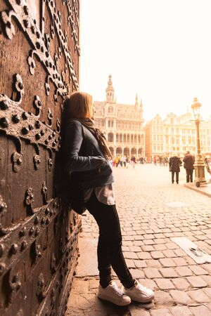 A young woman stands near the old gate in the heart of Brussels and looks at the King house and the Grand Place at sunset, Belgium.