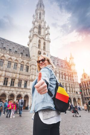 Young happy cheerful woman showing thumb up against the backdrop of the Grand Place in Brussels, Belgium Imagens
