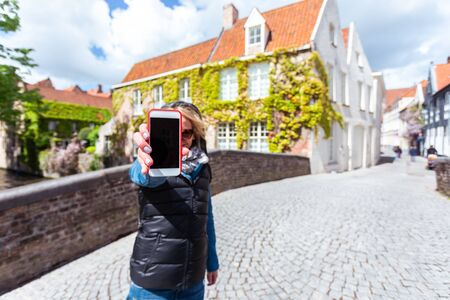 A woman stands on a street in the historic center of Bruges and shows the phone screen., Belgium