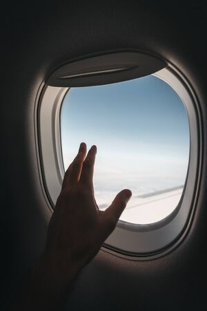 Porthole window in the plane with a mans hand during the flight. Reklamní fotografie