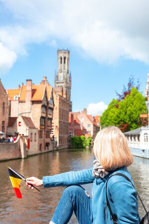 A young woman with the flag of Belgium in her hands is enjoying the view of the canals in the historical center of Bruges. Reklamní fotografie